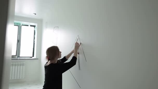 der Künstler zeichnet eine geometrische Figur an die Wand