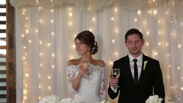 Novomanželé drží šampaňské ve svých rukou