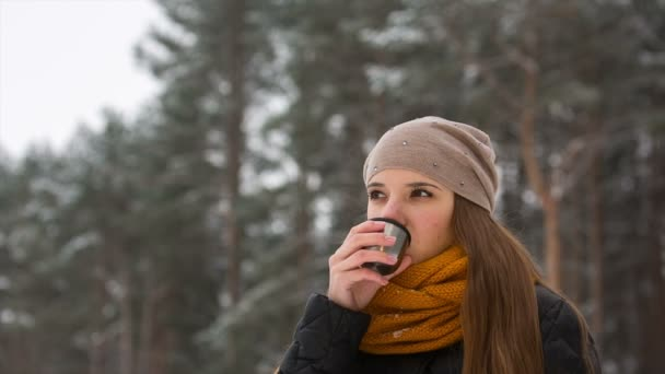 Face of girl with hot drink outdoors in winter.