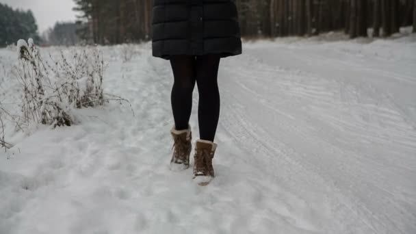 Legs of woman walking on snow with footprints on snowy day