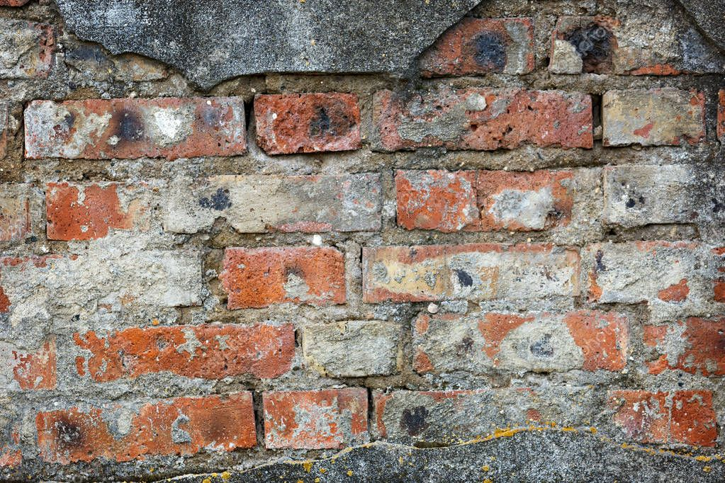 Wall of old red brick with remains of light-coloured plaster.