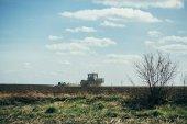 Farmář v traktoru, přípravu půdy s Záhonový kultivátor, slunce výstřel