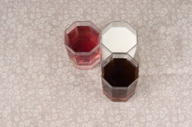 Various drinks in three glasses on the background of a linen tab