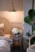 Modern stílus hálószoba belső világos színekben. Nagy ágy fehér lepedővel, egy elegáns, klasszikus szobában. Mellette egy fa szék, virágok egy üvegvázában, és egy csillár..