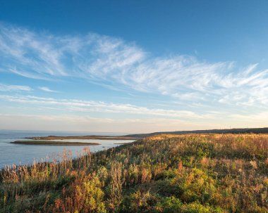Autumn landscape of the sea coast , blue sky with beautiful clouds, the coast overgrown with autumn colorful shrubs. Sunny day.