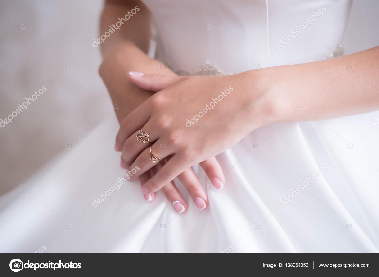 Joven novia en vestido de novia sostiene suavemente las manos con ...