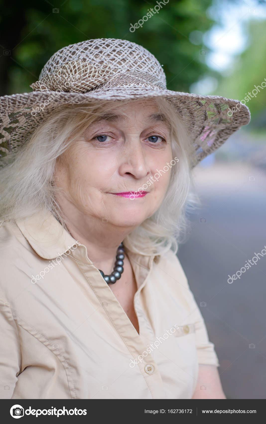 Ritratto di una donna anziana con i capelli grigi in un cappello e beige  vestito nel parco — Foto di elvirkindom yandex.ru 45dd5a15a709