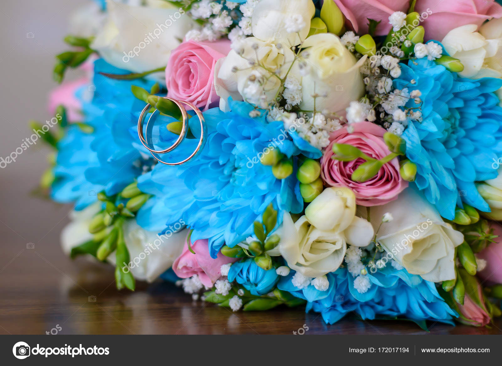 Engagement Rings And Wedding Bouquet On A Wooden Table Stock Photo