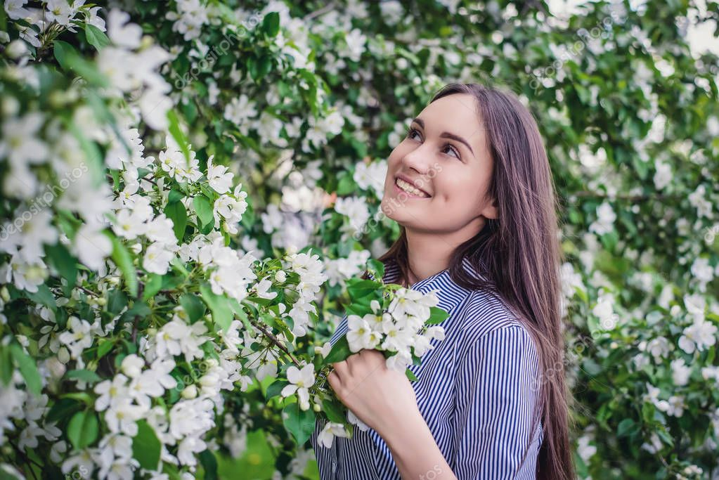 Beautiful young girl near blooming apple trees in spring