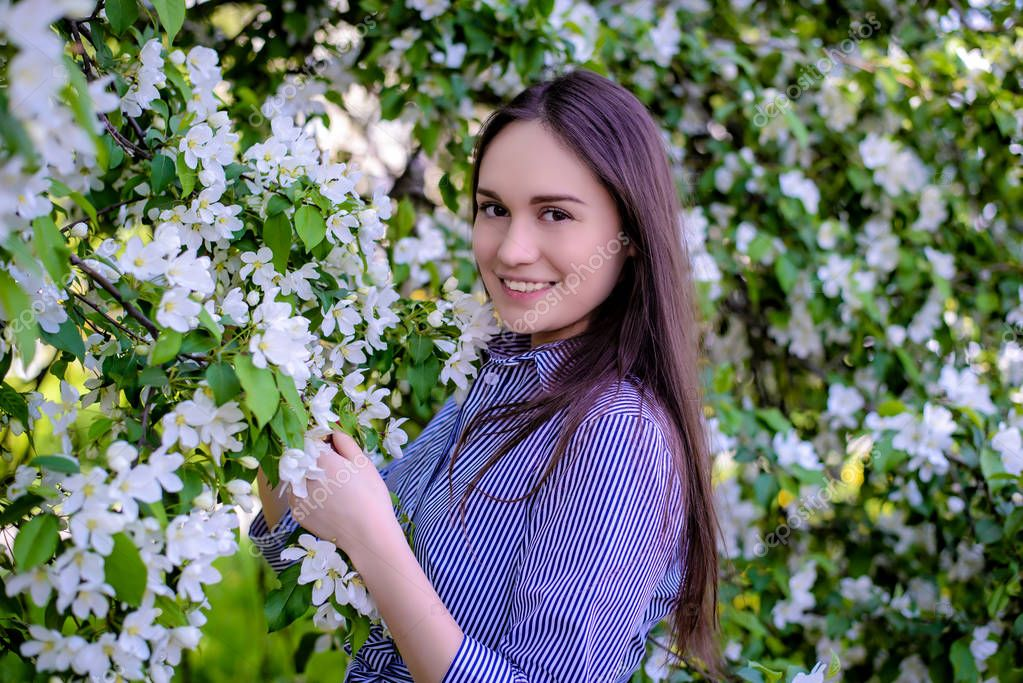 Beautiful girl near blooming apple trees in spring