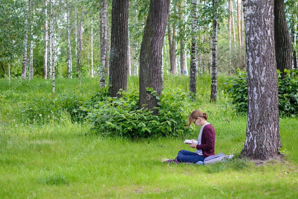 Russia, Kazan, June 14, 2017: girl reading a book on the grass in the park