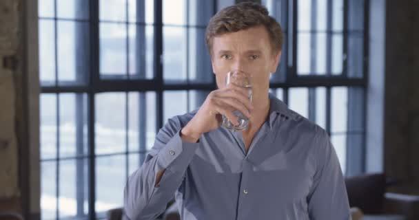 Zpomalený pohyb portrét úspěšný podnikatel pití čisté pitné vody v úřadu s úsměvem. Držte sklenici s vodou. Podnikatel série. 4k 4096 x 2160
