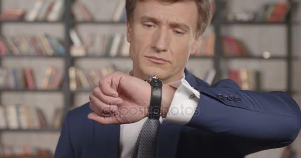 Slow Motion portrét z úspěšných jistý podnikatel kontrola času při pohledu na své hodinky a s úsměvem na kameru. Podnikatel série. 4k Uhd 4096 x 2160.
