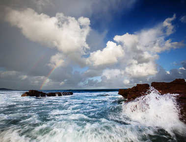 Vibrant seascape view at Scottburgh, South Africa, with a double rainbow and splashing water.