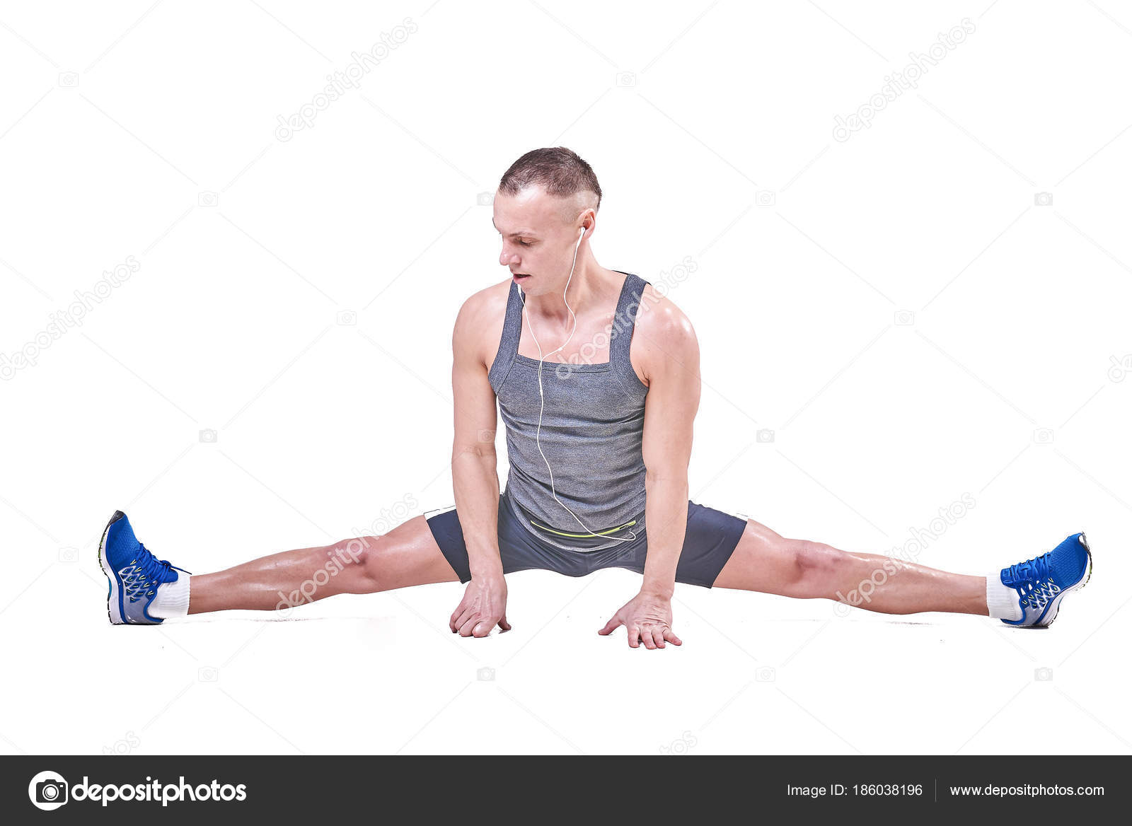 Beautiful man performs side splits in sportswear isolated on a white