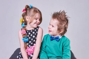 Beautiful little boy and girl happily smiling and looking at each other