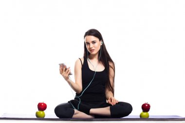 Girl is engaged in yoga on a white background, music, headphones, concept of health