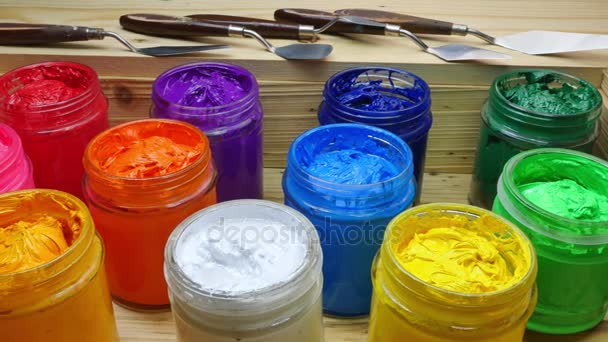 colorful of Plastisol Ink in the clear glass can on the wooden box for screen print tee shirt. Plastisol ink useful in tee shirt factory and in industry for export