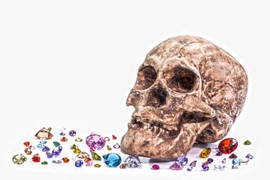 you can not take anything with you when you die.head skull on diamonds beside orb in white background.