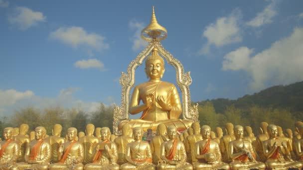 Řada zlaté sochy Buddhy mezi mnoha malými sochami Buddhy na venkově, veřejný chrám s názvem MAKHA BUCHA BUDDHIST MEMORIAL PARK v Nakornnayouk, Thajsko