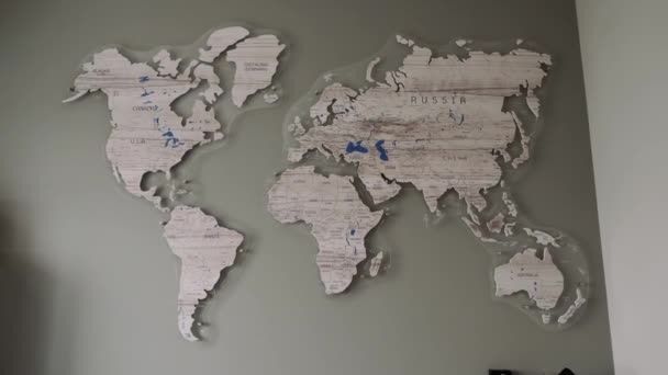 The camera slowly approaches the wall map of the world