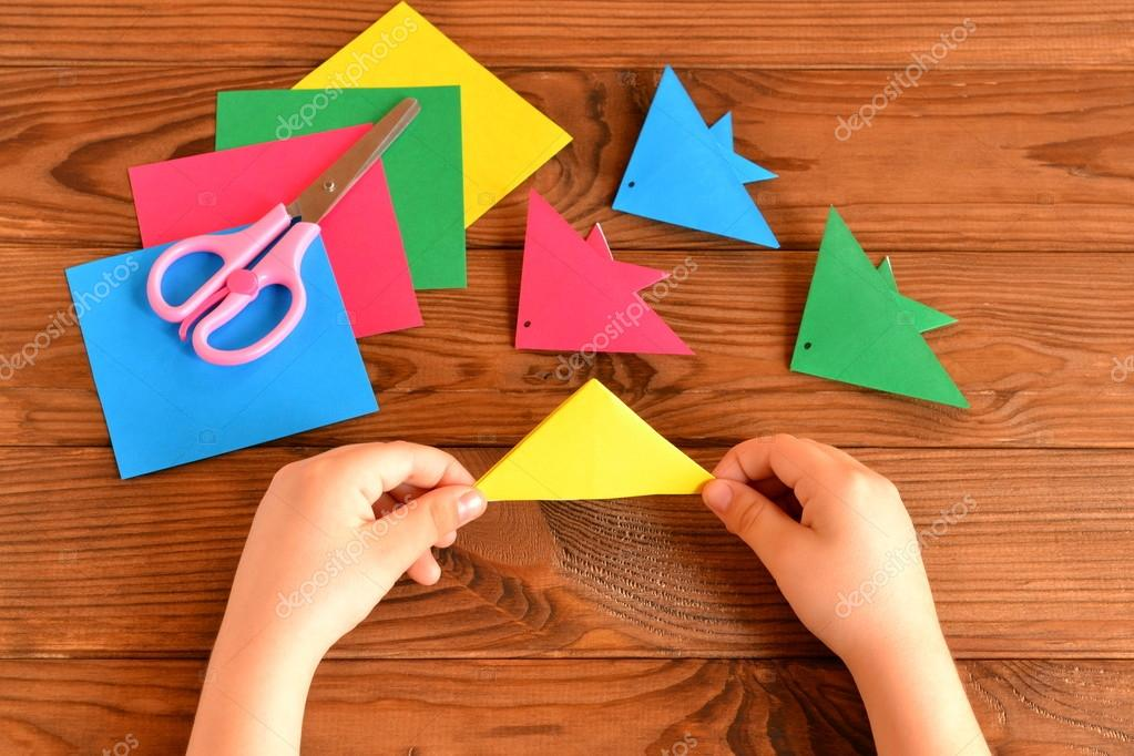 Origami colorful fish, paper sheets, scissors. Child holds paper ...