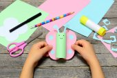 Photo Child holding colored paper butterfly in hands. Child shows a fun paper diy. Stationery on an old wooden background. Preschool paper and glue crafts activities. Children creative abilities development