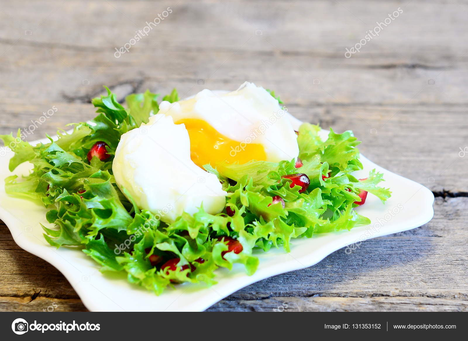 Poached egg, frise lettuce leaves with pomegranate seeds and olive