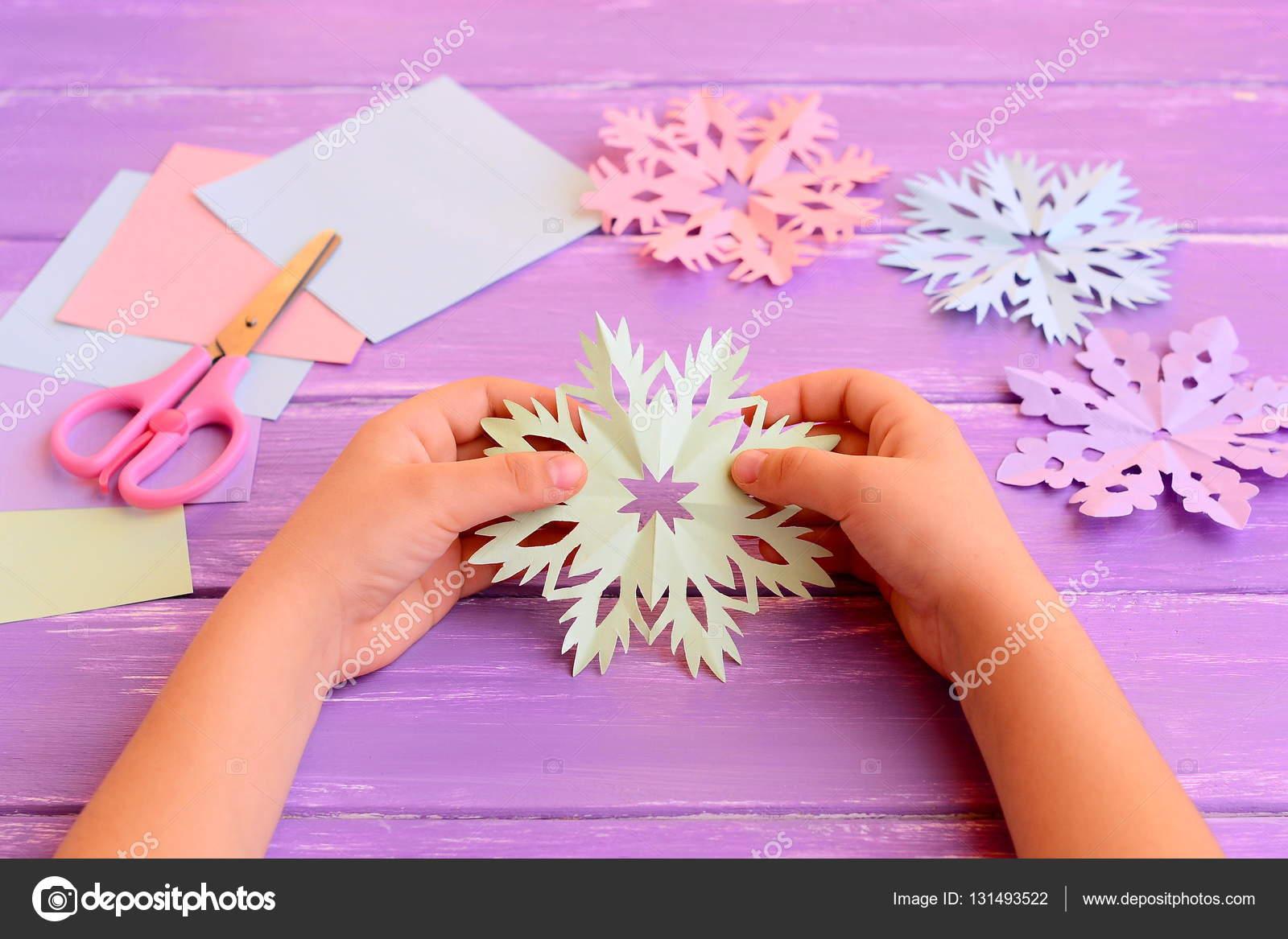 Fiocchi Di Neve Di Carta Facili : Il bambino tiene un fiocco di neve di carta nelle mani il bambino