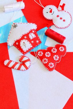 Cute Christmas tree ornaments. Felt house, Christmas tree, candy cane ornaments, red and white thread, needle on felt background with copy space for text. Kids winter holiday background. Closeup