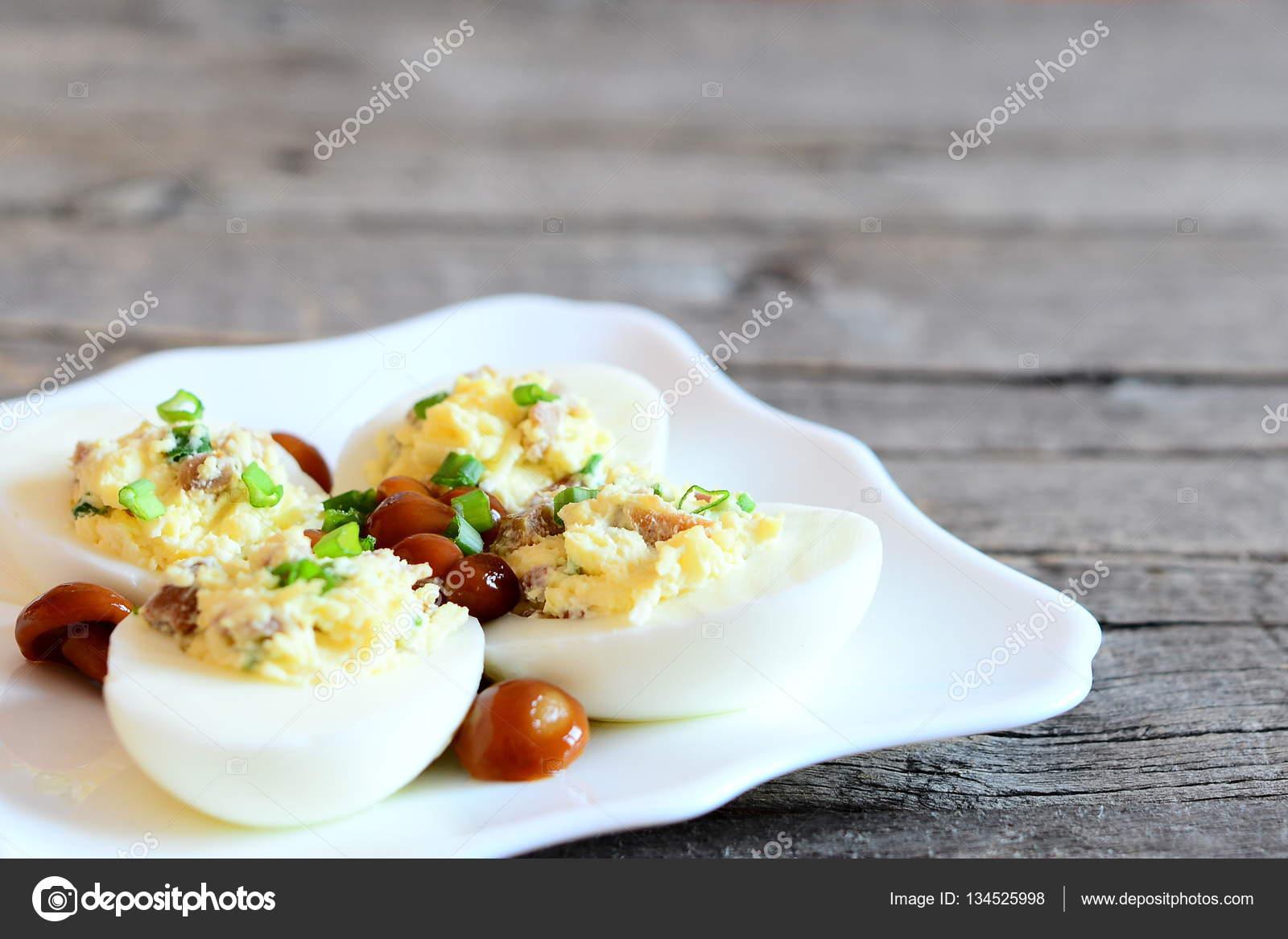 Heerlijke deviled eieren op een bord en op oude houten achtergrond