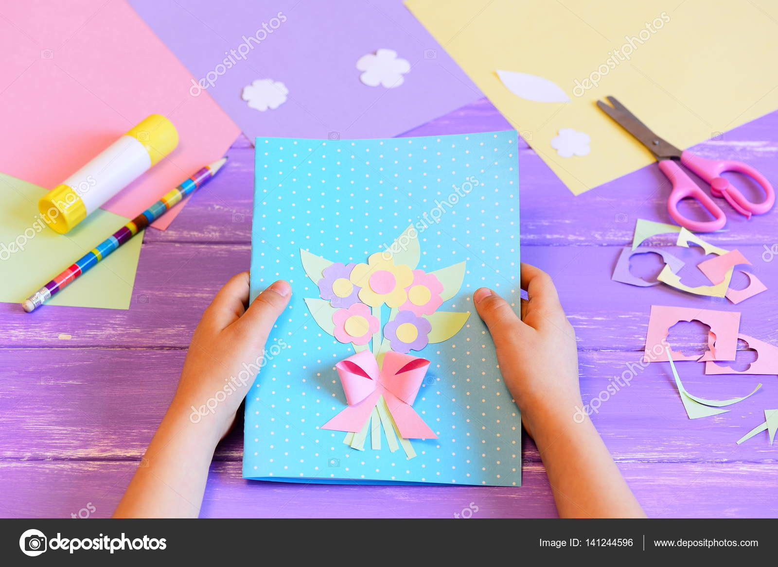 Small child made a greeting card with flowers for mom child holds a small child made a greeting card with flowers for mom child holds a card in his hands tools and materials for childrens art creativity on table m4hsunfo