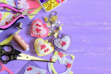 Beautiful hearts and flowers keyring. Homemade felt and fabric keyring or bag charm. Organizer with plastic flowers, scissors, pliers, felt set, fabric, thread. Wooden background with copy space