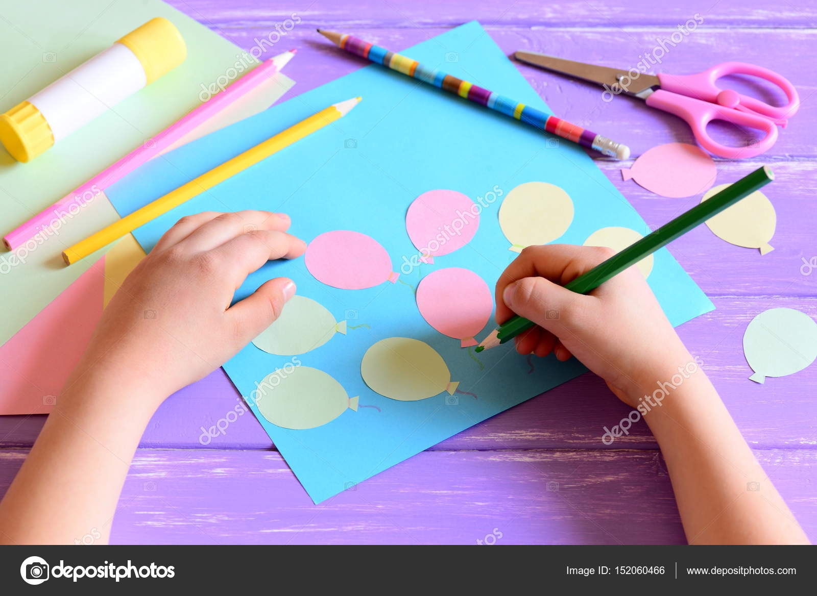 Small child doing a paper card  Child holds a pencil in hand  Card