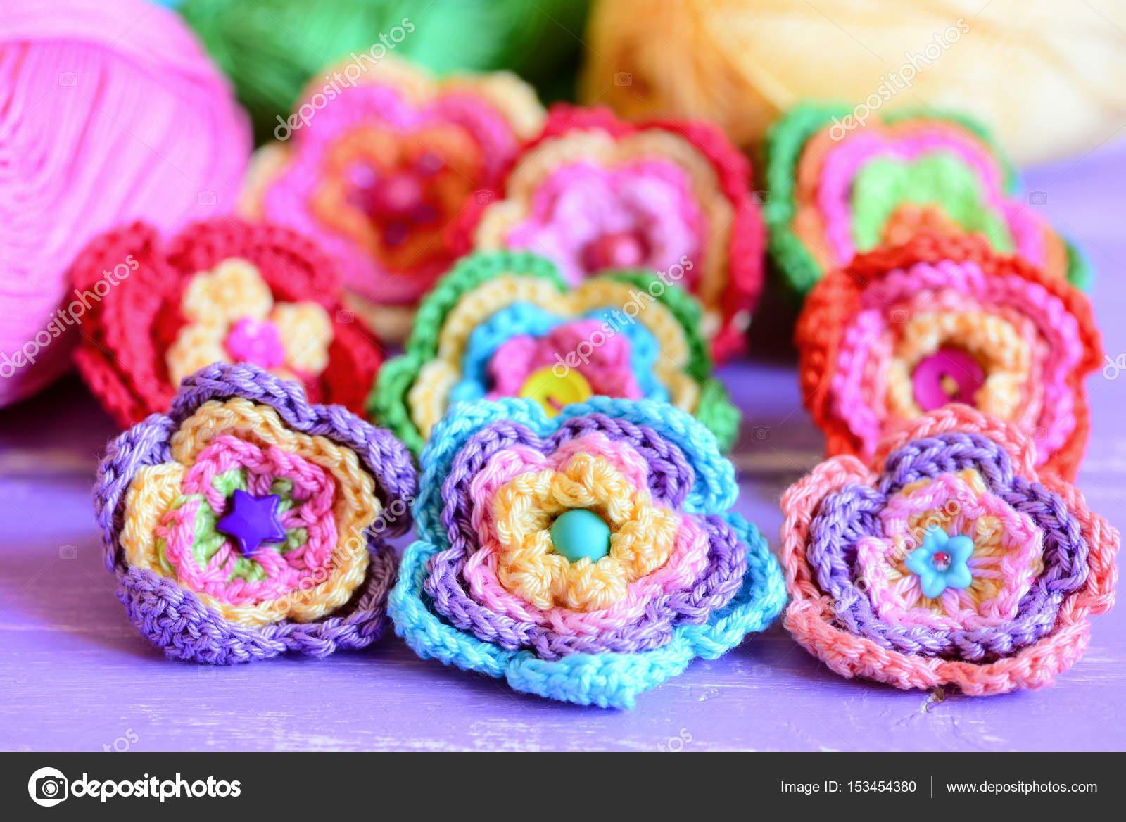 Lebendige Häkelblumen auf lila Hintergrund aus Holz. Häkelblumen aus ...