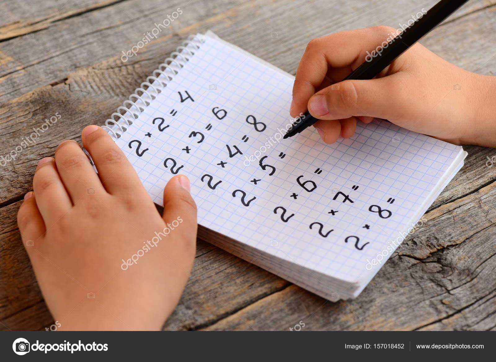 Kind löst Multiplikation Beispiele. Kind hält eine Markierung in der ...