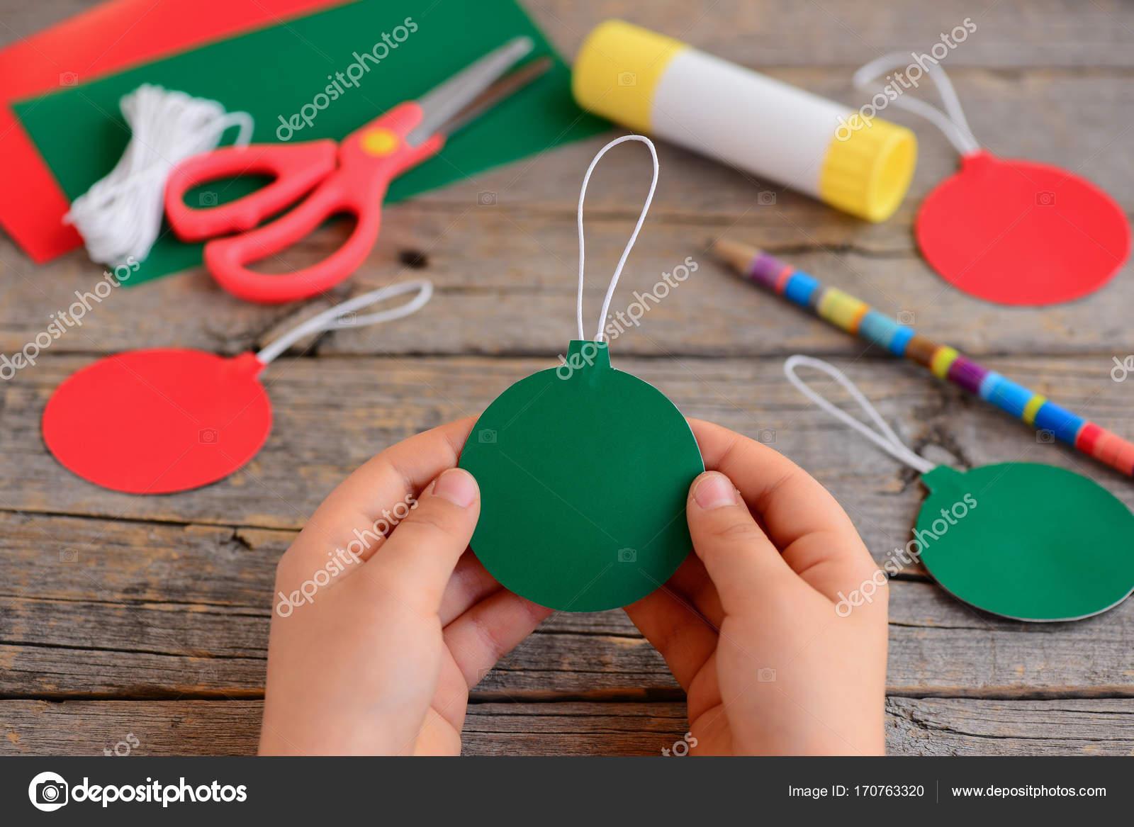 Kind Hat Rote Und Grune Weihnachtskugeln Aus Pappe Kind Halt