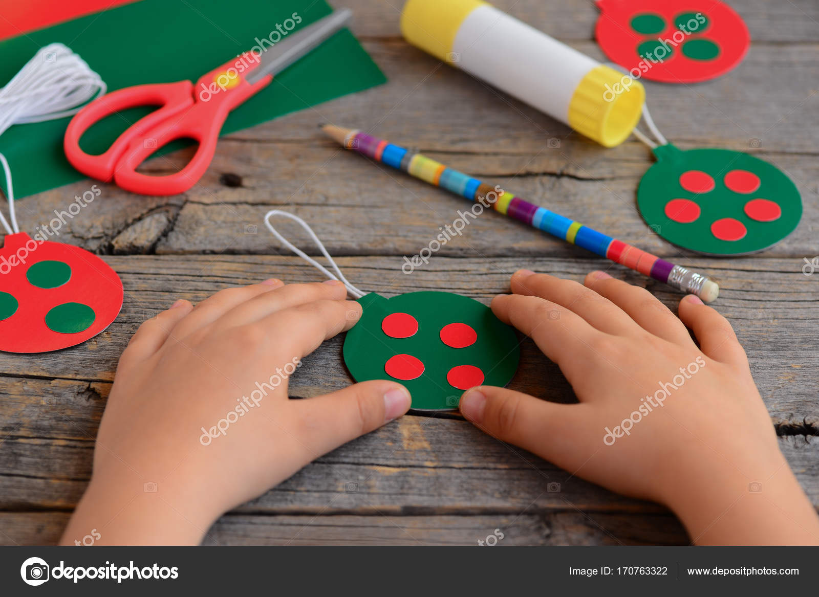 Niño hizo brillantes bolas de Navidad de cartulina. Niño muestra la ...