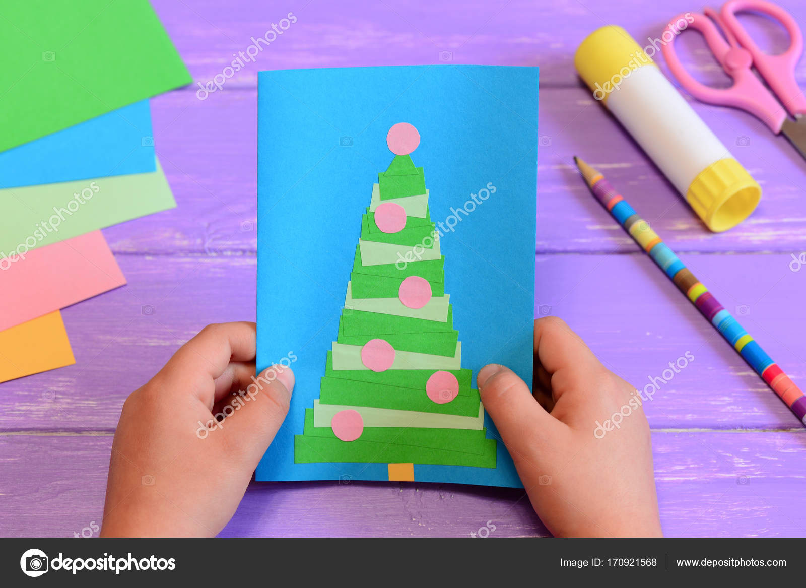 Child holds a christmas greeting card in his hands child made a child holds a christmas greeting card in his hands child made a paper greeting card with a christmas tree stationery on a table kristyandbryce Gallery