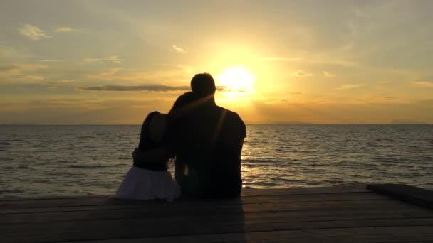 Romantický pár na pláži při barevném západu slunce na pozadí