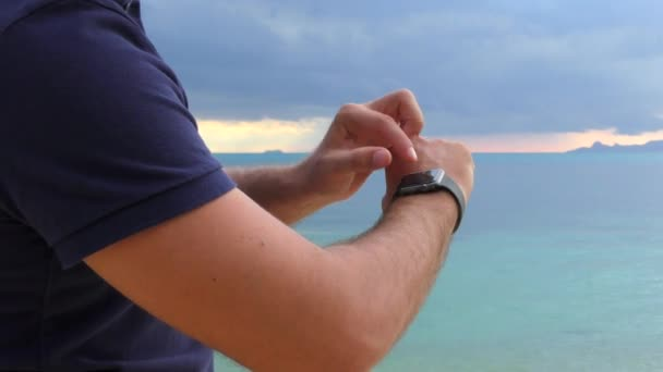 Close-up of a man s hand with smart watch, uses a smart watch on the sea background