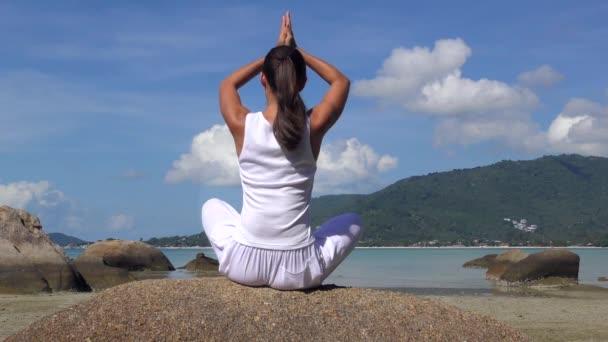 Fiatal nő meditál a tengeren