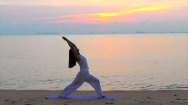Asian Woman Practicing Yoga at the Sunset Sea