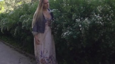 Young Girl Walking Near Brush With White Flowers Tree Slow Motion