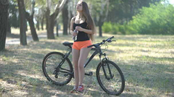 4K Teen Girl Standing With Her Bicycle On A Park And Drink Water
