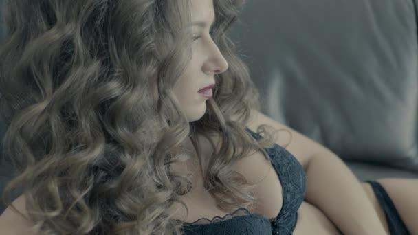 Nahaufnahme Porträt eines jungen Mädchens in schwarzen Dessous auf dem Bett im Hotelzimmer slow moti