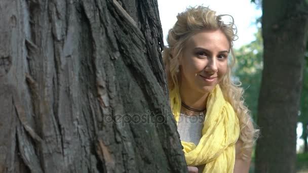 Egy lány a szeplő úgy néz ki, egy fa mögül.