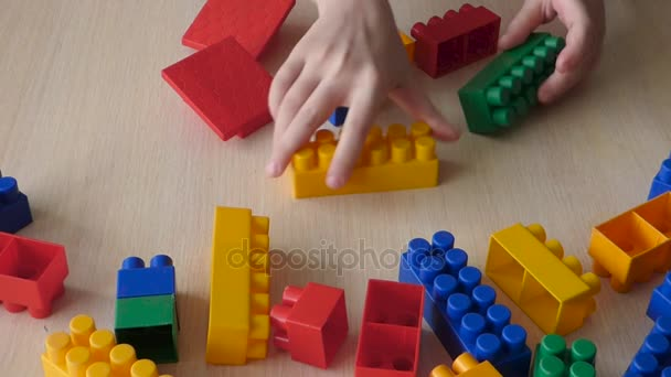 Child create toy buiding from plastic blocks.