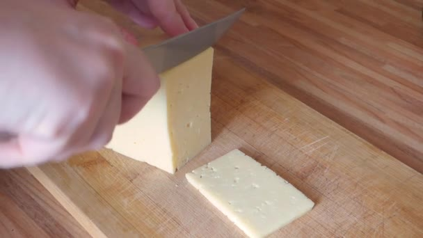 Women hands cutting cheese on wooden board