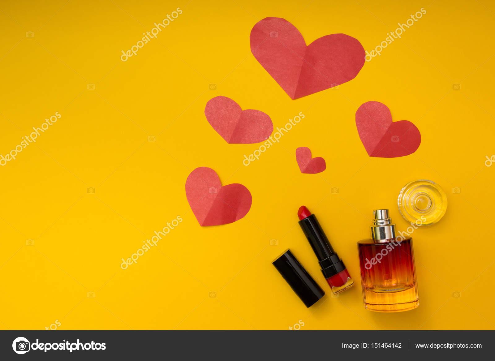 Corazón, lápiz labial y perfume sobre un fondo amarillo — Fotos de ...
